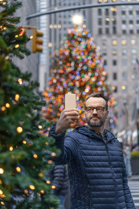 christmas facts -Male taking selfie against Christmas tree in city.