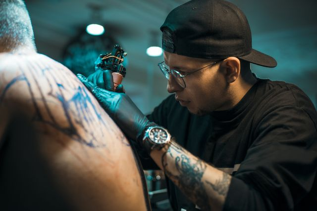 male tattoo master in black cap and glasses tattooing male back in tattoo salon