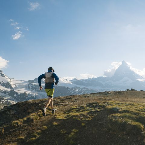 Male trail runner ascends above glaciated landscape