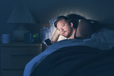 male using smartphone in bed at night