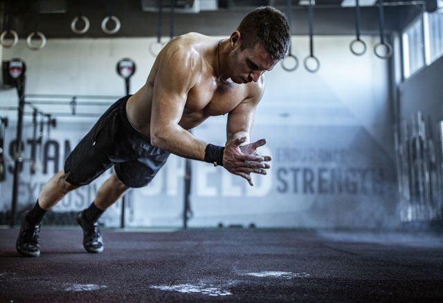 young athletic man exercising push ups while clapping his hands in a gym
