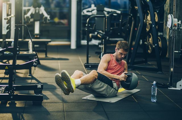 young male athlete making an effort while doing sit ups with medicine ball in a health club