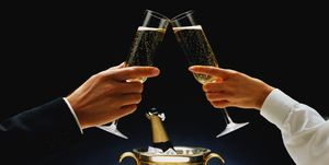 Man and woman holding champagne glasses, toasting, close-up