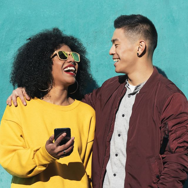 man and woman laughing while using mobile phone while standing against turquoise wall