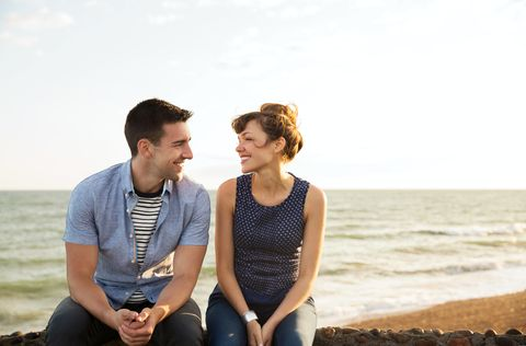Man and woman sat on wall together