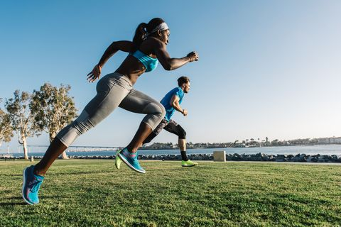 Man and young woman training, sprinting on coast, downtown San Diego, California, USA