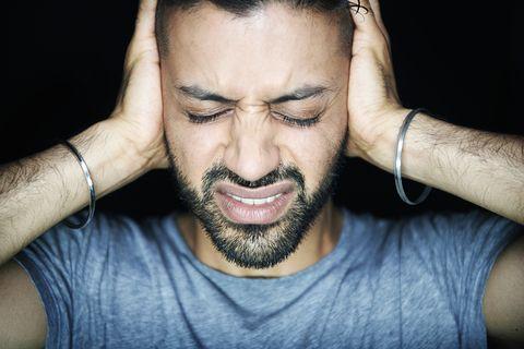man blocking ears looking stressed