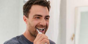 Man brushing teeth smiling