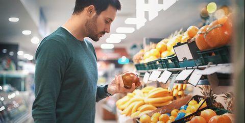Man buying fruit in supermarket.