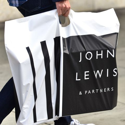 A man carrying a John Lewis and Partners shopping bag at...