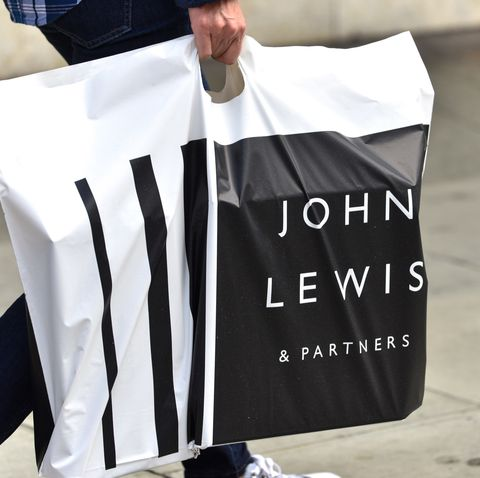 a man carrying a john lewis and partners shopping bag at