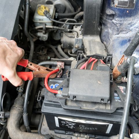 Man charging a car battery with a jumper cable