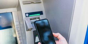 Man checking his smartphone screen near ATM machine