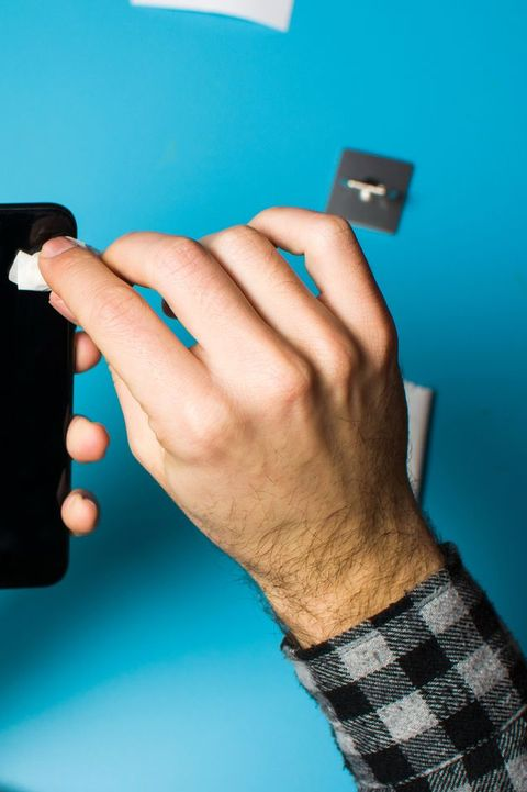 Man cleaning phone screen to apply protective glass