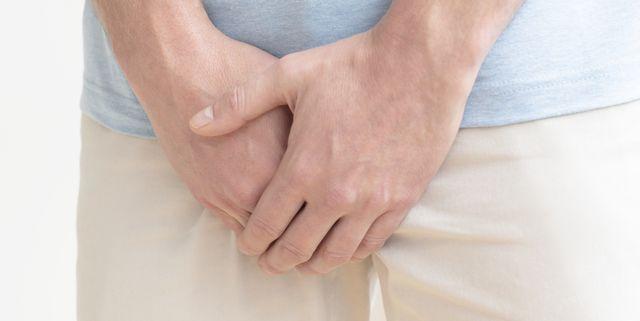 man clutching his crotch