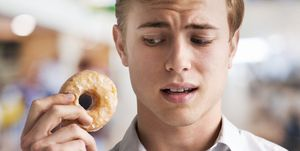 Man contemplating biting a sugar coated donut
