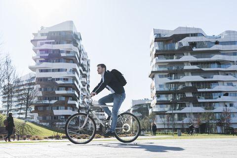 man cycling past multi storey building, milan, lombardia, italy