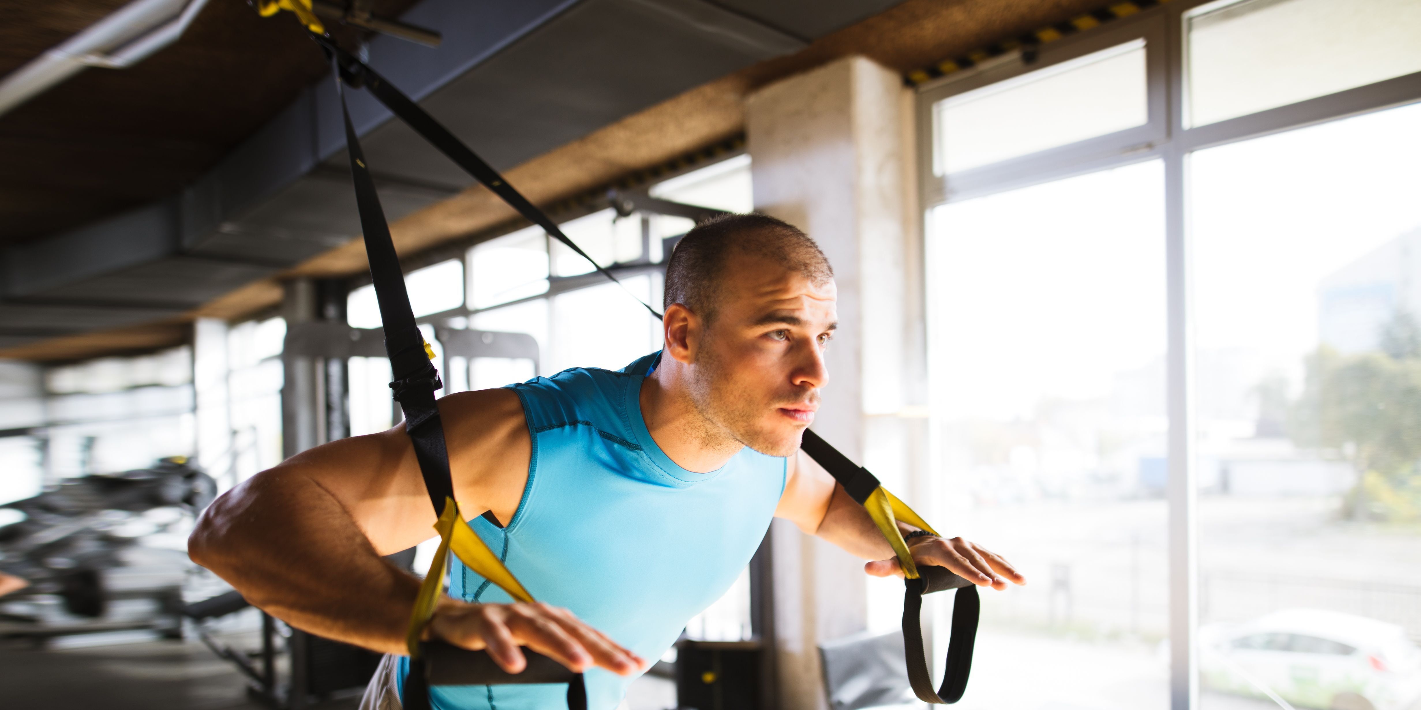 Man doing arm exercises with suspension straps at gym
