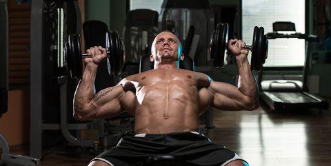 Man doet incline bench press met isometric hold