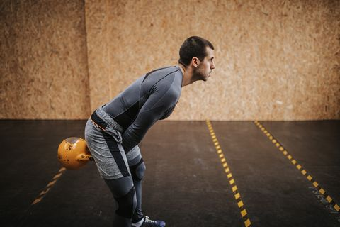 Man doing exercise with kettle bell in gym