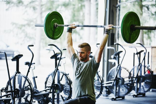 man doing lunges with barbell overhead in gym