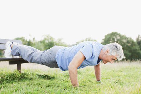 Man doing push-ups in field