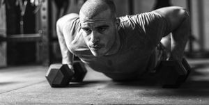 Man doing push ups indoors on dumbbells in gym