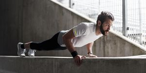 Man doing push-ups on concrete wall