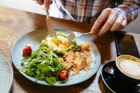 man eating avocado toast with egg, salmon and arugula salad for brunch at the restaurant