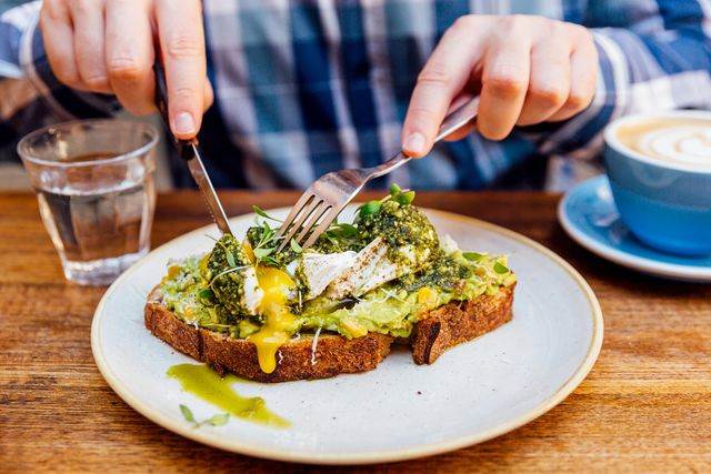 man eating avocado toast with poached egg, close up