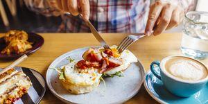 Man eating breakfast with egg, bacon, arugula on brioche bun and coffee