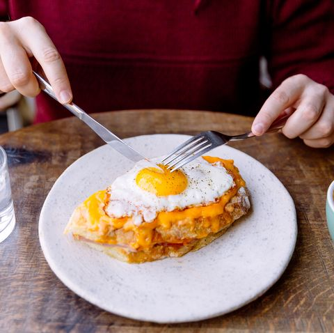 man eating croque madame sandwich with cheese and fried egg