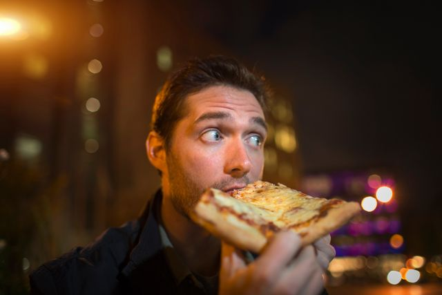 man eating pizza on city street