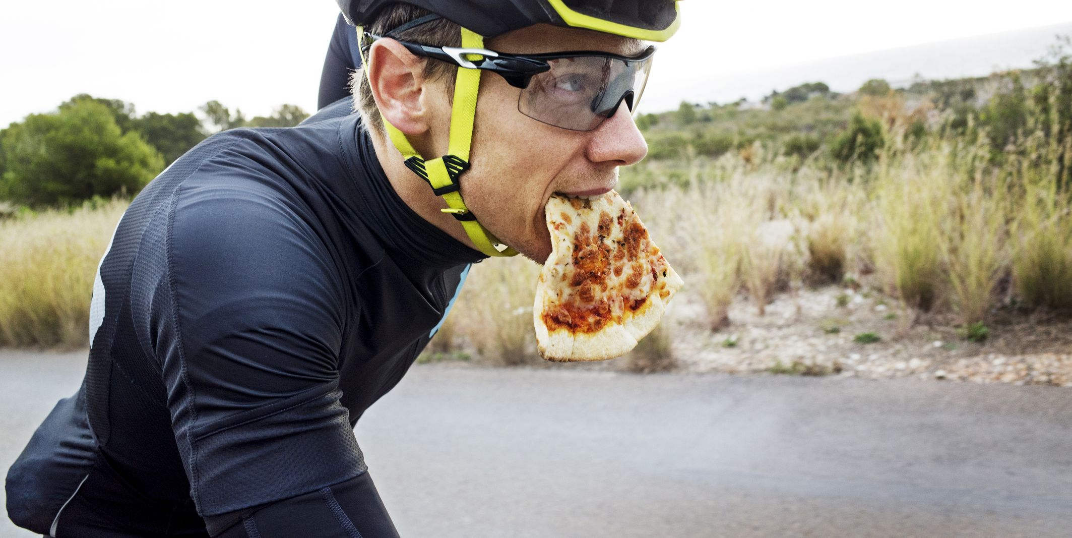 Man eating pizza while cycling on street against clear sky