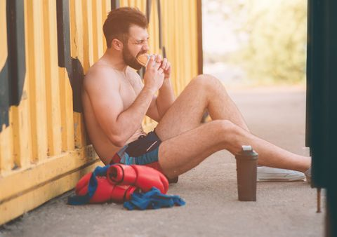 Man eats a hamburger after a workout. Very hungry, fatty and unhealthy food.