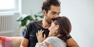 Man embracing girlfriend while kissing on her forehead at home
