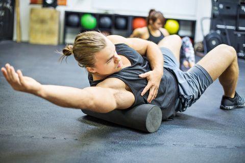 Man exercising on foam roller in gym