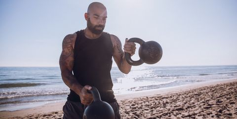 Man Exercising With Kettlebells At Beach Against Sky