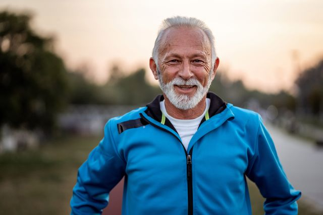 active senior man is looking at camera and smiling on the running track outdoors