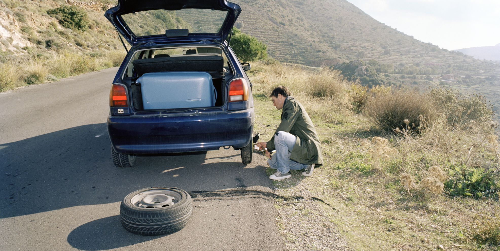 Man fixing flat tire, car packed for road trip