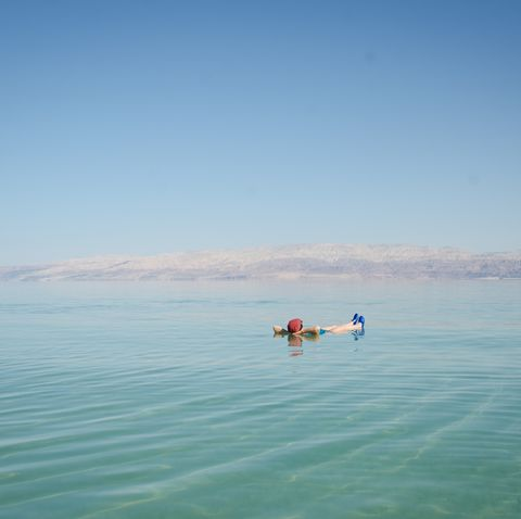 Man Floating In Dead Sea Against Clear Blue Sky