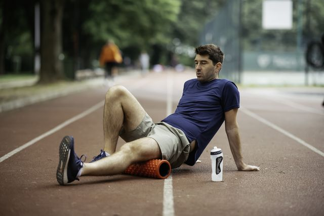 man foam rolling athlete stretches using foam roller
