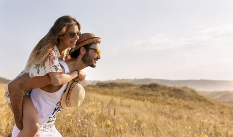 Man giving his girlfriend a piggyback ride in nature