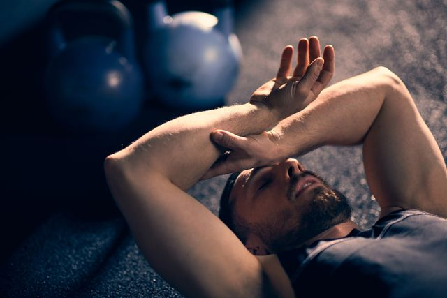 tired athlete lying down with hand on his head at home