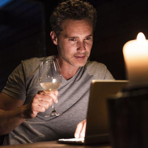 Man having glass of white wine looking at laptop