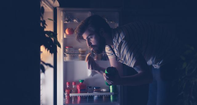 man having snack and drinking beer late night in front of the refrigerator