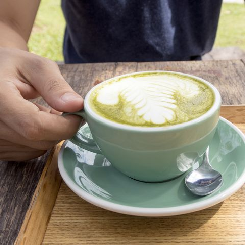 man holding a cup of hot green tea latte on wooden table.