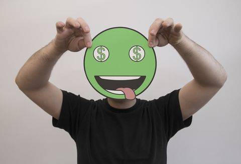 man holding a green dollar sign emoticon face in front of his face