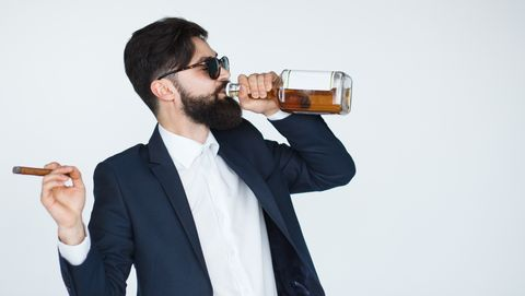 Man holding a whiskey and drinking from the bottle
