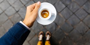 Man holding cup of espresso coffee, personal perspective view